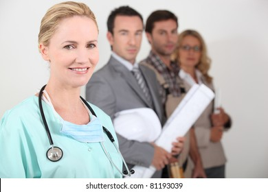 Female nurse stood next to four professionals from different backgrounds