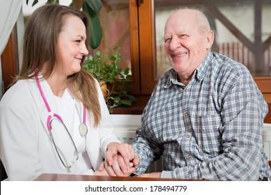 Female nurse taking care of senior old man