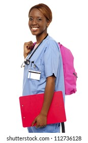 Female nurse under training holding her backpack and clipboard to write down notes