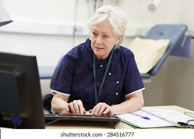 Female Nurse Working At Desk In Office