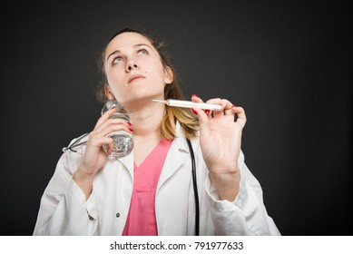 Female nutritionist cooling herself having fever holding thermometer on black background with copyspace advertising area