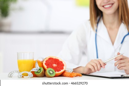 Female nutritionist with fruits working at her desk