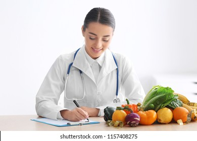 Female nutritionist sitting at table with clipboard and healthy products on white background