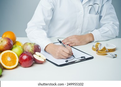 Female nutritionist at work writing documents on a clipboard with fresh fruit on foreground