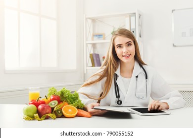 Female nutritionist working on digital tablet in office. Beautiful woman dietitian typing, counting calories or writing diet plan, copy space. Healthy eating concept