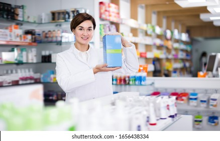 Female offering products of body care in pharmacy