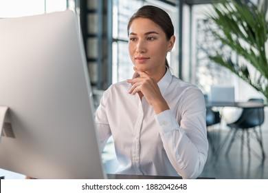 Female office manager in white shirt in office interior background, beautiful woman office worker. Woman working with computer in big office, concept of work