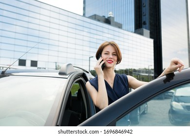 Female in office suit ariives at work by car and smiles