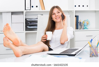 Female office worker with bare feet on desk talking on phone during coffee break
