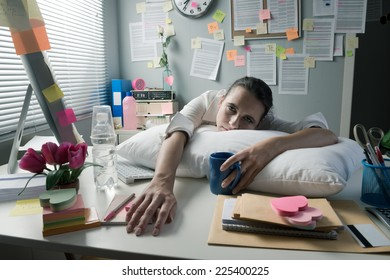 Female office worker bent over with head leaning to a wall and negative business chart.
