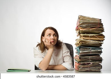 Female office worker with chin in hands staring at huge pile of files and folders awaiting her attention