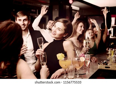Female office worker is drinking cocktails with colleague at corporate event in bar.
