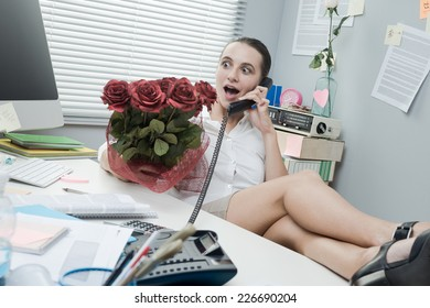Female office worker feet up on desk talking on the phone and holding roses.