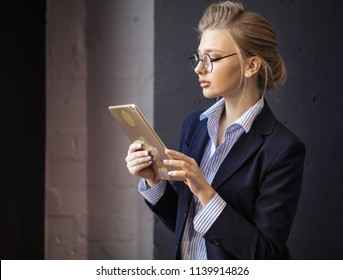 female office worker looking at the photos in the tablet. close up side view photo. studing concept. side view photo