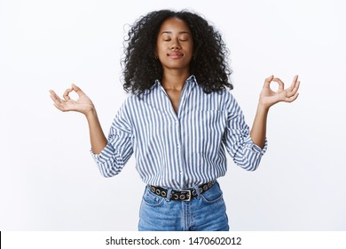 Female office worker meditating during lunch keep feelings emotions under control, do breathing practice yoga, hands sideways zen gesture nirvana pose close eyes relieved, release stress
