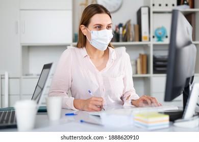 Angestellte von Frauenbüros mit Schutzmaske haben einen produktiven Arbeitstag im Amt