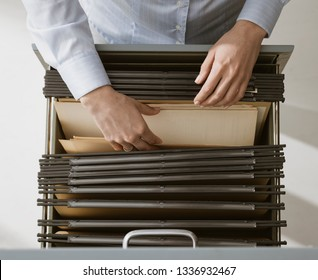 Female office worker searching files and paperwork in the archive, she is checking folders in a filing cabinet