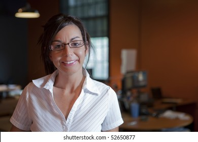 A female office worker wearing eye glasses is standing in an office environment. Horizontal shot.