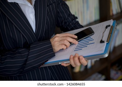 Female office worker working on her presentation standing reading the report printed on paper. looking at sales charts and documents.