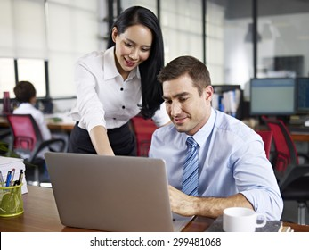 female office worker working together with caucasian expat colleague in office.