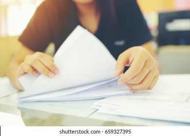 Female office workers holding  are arranging documents of unfinished documents on office desk, Stack of business paper. - Shutterstock ID 659327395