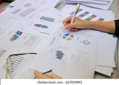 Female office workers holding are arranging documents of unfinished documents archive analyzing the market and considers on the size of future profits on table office. Stack of business paper.