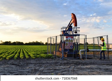 A female oil industry engineer at work on an European oil well during twilight