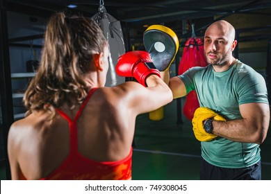 Female on boxing class with her male instructor