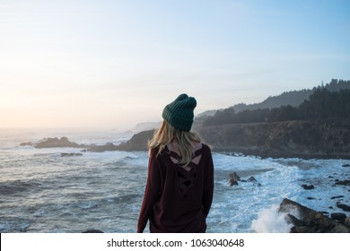 female on a cliff side looking at the ocean at sunset