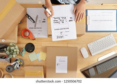 Female online store owner writing address and name of customer on parcel