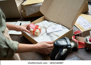 Female online store small business owner seller holding gift packing package post shipping box preparing delivery parcel on table. Ecommerce dropshipping holiday presents sale concept. Closeup.