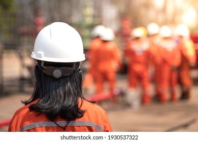 A female operation supervisor wearied white safety hardhat helmet is coming with blurred of other workers group in far distance. Industrial working concept and background photo.