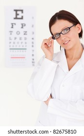 A female optician with glasses and eye test in office