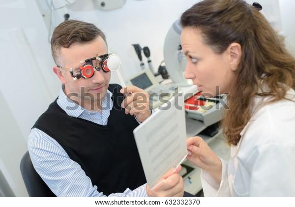 female optician in surgery giving man eye test