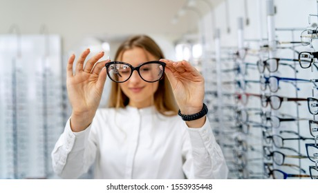 female optometrist, optician is standing with many glasses in background in optical shop. Stand with spectacles. Eyesight correction. Woman holds spectacles in hands. Closeup. - Shutterstock ID 1553935448