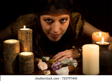 female Oracle with healing stones and Candles, concept Strength and Love