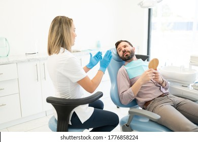 Female orthodontist discussing with mid adult man during treatment
