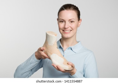 Female orthopedic shoemaker shows proudly a handmade wooden last