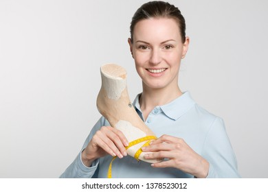 Female orthopedic shoemaker works on a handmade wooden last