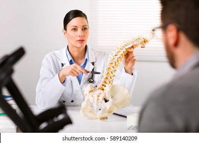 Female Orthopedic surgeon explaining a back injury or disease to a male patient on crutches with the help of a human spine