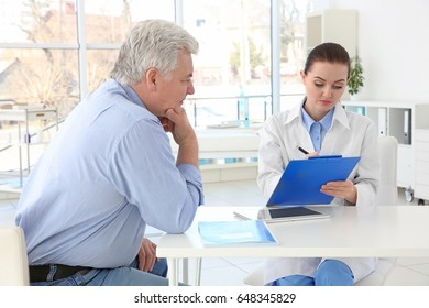 Female orthopedist examining senior man in clinic