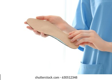 Female orthopedist with insole on white background, closeup