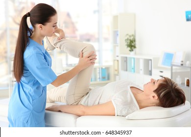 Female orthopedist massaging middle-aged woman in clinic