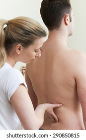 Female Osteopath Treating Male Patient With Back Problem