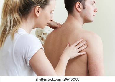 Female Osteopath Treating Male Patient With Shoulder Problem