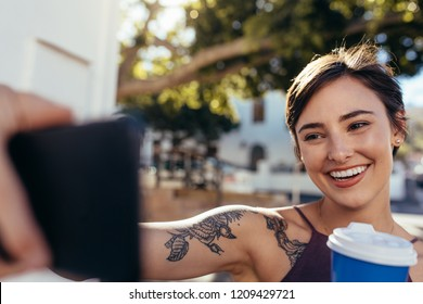 Female outdoors having coffee and vlogging using her smart phone. Social media influencer recording her activities as a content for vlog. Taking selfie with her smart phone.
