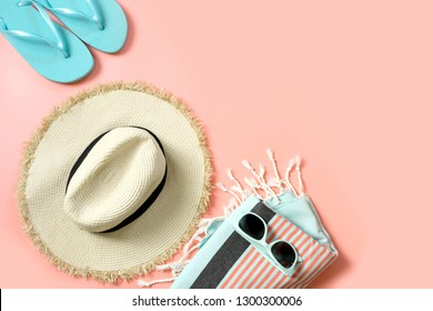Female outfit for beach. Straw sunhat and sun glasses on punchy pink with space for text. Summer tropical concept.