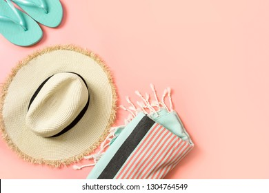 Female outfit for beach. Straw sunhat and beach slaps on punchy pink with space for text. Summer tropical concept.