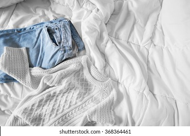 Female outfit laid out on bed, morning light