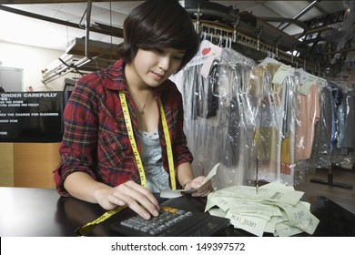 Female owner using calculator while holding bill in laundry